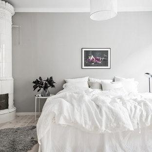 Minimalistisk inredning av ett mellanstort huvudsovrum, med grå väggar, ljust trägolv, en öppen hörnspis, en spiselkrans i trä och grått golv