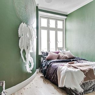 Nordisk inredning av ett litet huvudsovrum, med gröna väggar, ljust trägolv och beiget golv