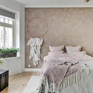 Minimalistisk inredning av ett mellanstort huvudsovrum, med beige väggar, ljust trägolv och beiget golv
