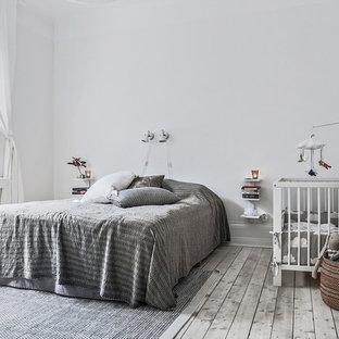 Bild på ett stort skandinaviskt huvudsovrum, med vita väggar, ljust trägolv och grått golv