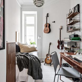 Nordisk inredning av ett litet sovrum, med vita väggar, ljust trägolv och vitt golv