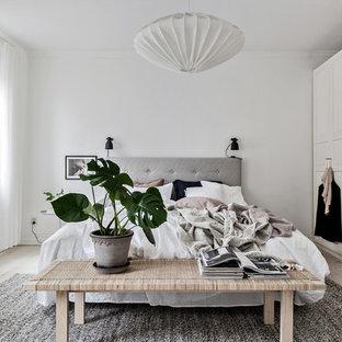 Foto på ett mellanstort skandinaviskt huvudsovrum, med vita väggar, ljust trägolv och beiget golv