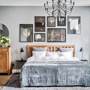 Idéer för att renovera ett stort vintage huvudsovrum, med grå väggar, mellanmörkt trägolv och beiget golv