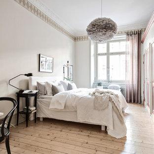 Idéer för stora minimalistiska sovrum, med beige väggar och ljust trägolv