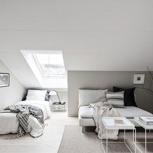 Bild på ett litet skandinaviskt sovrum, med grå väggar, ljust trägolv och grått golv