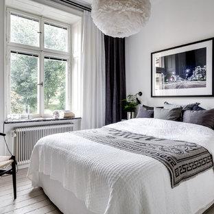 Idée de décoration pour une chambre parentale nordique de taille moyenne avec un mur blanc, un sol en bois peint et un sol blanc.