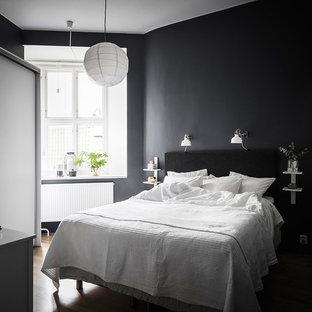 Inspiration för små skandinaviska gästrum, med svarta väggar, mellanmörkt trägolv och brunt golv