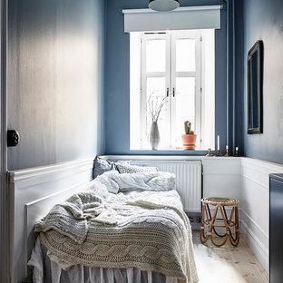 Inredning av ett skandinaviskt gästrum, med blå väggar