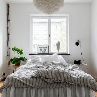 Bild på ett litet nordiskt sovrum, med vita väggar, ljust trägolv och beiget golv
