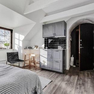 Foto på ett skandinaviskt sovrum, med vita väggar, mellanmörkt trägolv och brunt golv