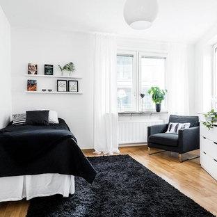 Idéer för ett mellanstort minimalistiskt gästrum, med vita väggar och mellanmörkt trägolv