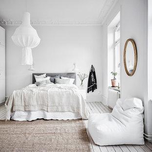 Стильный дизайн: спальня в скандинавском стиле с белыми стенами, деревянным полом и белым полом - последний тренд