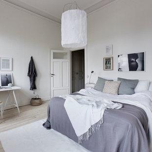 Idéer för ett skandinaviskt sovrum, med vita väggar, ljust trägolv och beiget golv