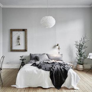 Idéer för att renovera ett stort nordiskt sovrum, med grå väggar och ljust trägolv