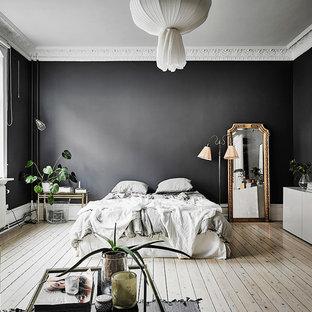 Cette photo montre une très grand chambre parentale scandinave avec un mur noir, un sol en bois clair et aucune cheminée.