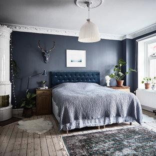 Inredning av ett minimalistiskt huvudsovrum, med blå väggar, ljust trägolv, en öppen vedspis, en spiselkrans i metall och beiget golv