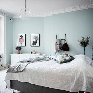 Foto på ett nordiskt sovrum, med blå väggar och vitt golv