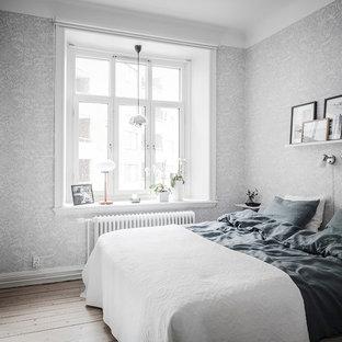 Inredning av ett skandinaviskt sovrum, med grå väggar, ljust trägolv och beiget golv