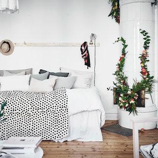Skandinavisk inredning av ett sovrum, med vita väggar, mellanmörkt trägolv, beiget golv och en öppen hörnspis