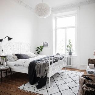 Nordisk inredning av ett mellanstort huvudsovrum, med vita väggar, mörkt trägolv och brunt golv