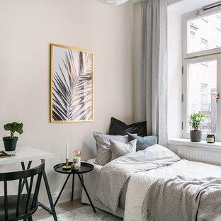 Nordisk inredning av ett litet gästrum, med vita väggar, beiget golv och ljust trägolv