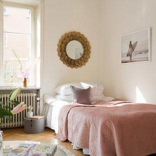 Idéer för att renovera ett nordiskt sovrum, med vita väggar och mellanmörkt trägolv