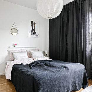 Idéer för mellanstora skandinaviska huvudsovrum, med mellanmörkt trägolv och brunt golv
