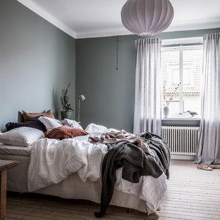 Exempel på ett stort nordiskt huvudsovrum, med grå väggar, ljust trägolv och beiget golv