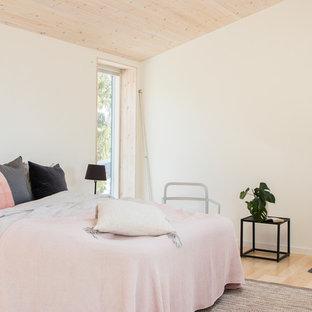 Foto på ett nordiskt huvudsovrum, med vita väggar, ljust trägolv, en öppen vedspis, en spiselkrans i metall och beiget golv