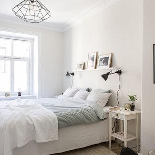 Modelo de dormitorio principal, nórdico, de tamaño medio, sin chimenea, con paredes blancas y suelo de madera clara