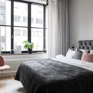 Inredning av ett modernt mellanstort sovrum, med vita väggar, ljust trägolv och beiget golv