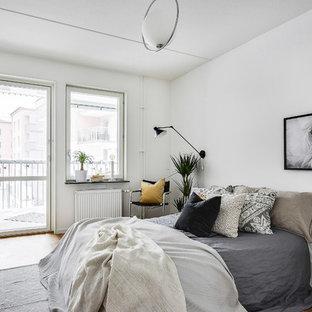 Idéer för att renovera ett minimalistiskt sovrum, med vita väggar, ljust trägolv och brunt golv