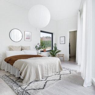 Idéer för nordiska sovrum, med vita väggar, ljust trägolv och grått golv
