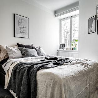 Immagine di una camera da letto scandinava con pareti bianche, parquet scuro e pavimento nero