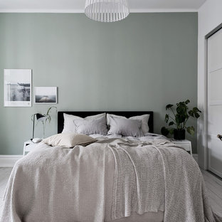 Photo of a large scandinavian master bedroom in Gothenburg with green walls, light hardwood floors and white floor.