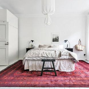 Skandinavisk inredning av ett stort huvudsovrum, med vita väggar, målat trägolv och vitt golv