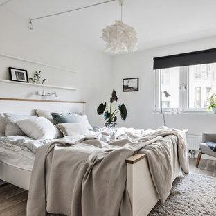 Idéer för ett minimalistiskt sovrum, med vita väggar, ljust trägolv och beiget golv