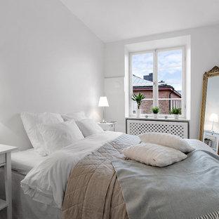 Foto på ett litet minimalistiskt huvudsovrum, med vita väggar