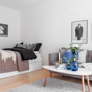 Foto på ett litet skandinaviskt sovrum, med vita väggar, mellanmörkt trägolv och brunt golv