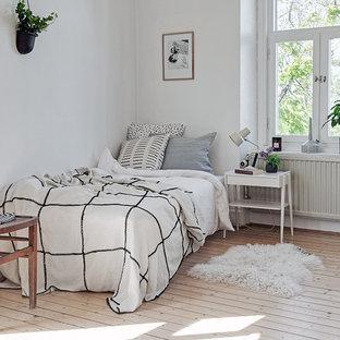 Idéer för ett mellanstort nordiskt gästrum, med vita väggar och ljust trägolv