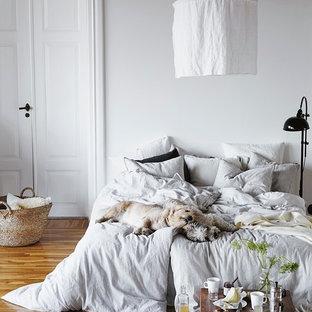Inspiration för ett stort skandinaviskt huvudsovrum, med vita väggar och mellanmörkt trägolv