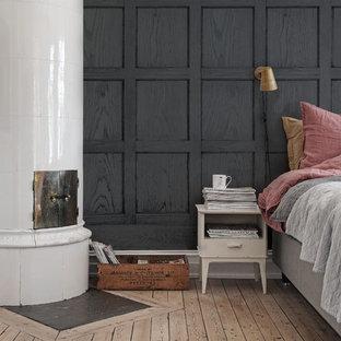 Imagen de dormitorio principal, moderno, de tamaño medio, con chimenea de esquina, paredes negras y suelo de madera clara