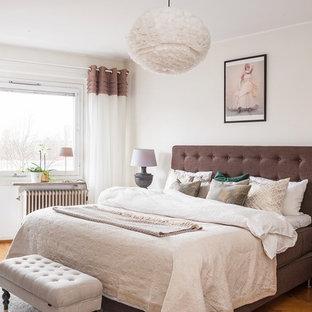 Exempel på ett mellanstort minimalistiskt sovrum, med vita väggar, mellanmörkt trägolv och brunt golv