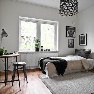 Nordisk inredning av ett mellanstort sovrum, med vita väggar, mellanmörkt trägolv och brunt golv