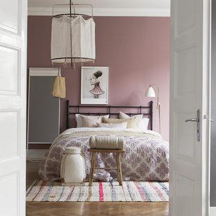 Klassisk inredning av ett mellanstort sovrum, med lila väggar och ljust trägolv