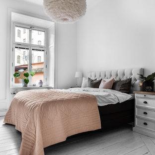 Bild på ett mellanstort nordiskt huvudsovrum, med vita väggar, målat trägolv och grått golv