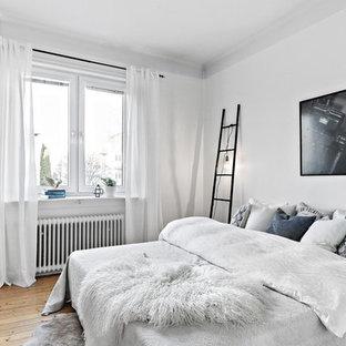 Exempel på ett nordiskt sovrum, med vita väggar, mellanmörkt trägolv och brunt golv