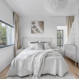 Idéer för mellanstora nordiska sovrum, med vita väggar, ljust trägolv och beiget golv