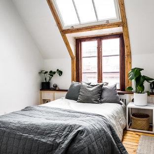 Skandinavisk inredning av ett huvudsovrum, med mellanmörkt trägolv, vita väggar och brunt golv