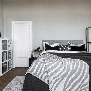 Bild på ett nordiskt huvudsovrum, med grå väggar, mörkt trägolv och brunt golv